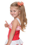 Little girl with her thumb up looks back Royalty Free Stock Photo