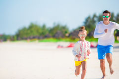 Little girl and her young father at tropical beach having fun Royalty Free Stock Photos