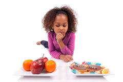 Little girl hesitating between fruits or  candy Stock Images