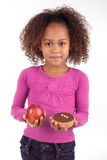 Little girl hesitating between fruits or candy Stock Photography