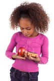 Little girl hesitating between fruits or candy Royalty Free Stock Photos