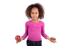 Little girl hesitating between fruits or candy Royalty Free Stock Images