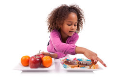 Little girl hesitating between fruits or  candy Royalty Free Stock Image