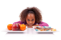Little girl hesitating between fruits or  candy Stock Photos