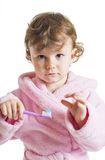 Little girl hesitating to brush her teeth Stock Images