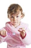 Little girl hesitating to brush her teeth. Three years old girl in pink dressing gown/bathrobe hesitating to brush her teeth Stock Images