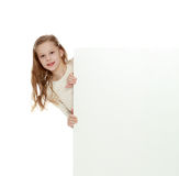 The little girl hid behind the banner. Royalty Free Stock Images