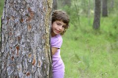 Little girl hide park tree trunk green outdoor Royalty Free Stock Images
