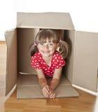 Little girl hiden inside a paper box stock photography