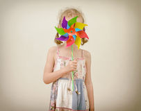 Little girl hides behind colorful pinwheel. Stock Image