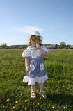 Little girl hides her face in yellow dandelions Stock Photography