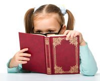 Little girl is hiding behind a book Royalty Free Stock Images