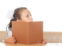 Little girl hiding behind book Royalty Free Stock Image