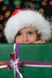 Little girl hiding. Behind a christmas gift Stock Photos