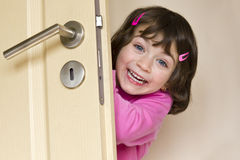 Little girl is hiding behind a door Stock Photos