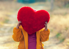 Little girl hiding behind heart shaped pillow Royalty Free Stock Photos