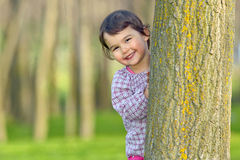 Little girl hiding behind a tree royalty free stock images