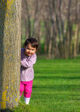 Little girl hiding behind a tree in a forest Stock Photos