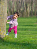 Little girl hiding behind a tree in a forest in spring Royalty Free Stock Photos
