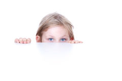 Little girl hiding behind white table. Blond little girl hiding behind white table Stock Photo