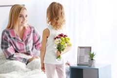 Little girl hiding bouquet of flowers for her mother behind back. Mother`s day concept Royalty Free Stock Photos