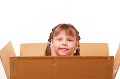 Little girl hiding in cardboard box Royalty Free Stock Photography