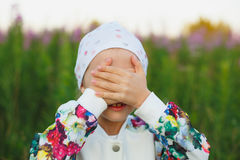 Little girl hiding face outdoor portrait. Beautiful little girl covering her eyes with her hands Royalty Free Stock Images