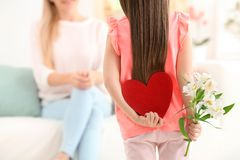 Little girl hiding felt heart and flower for Mother`s Day. Behind her back at home Royalty Free Stock Images