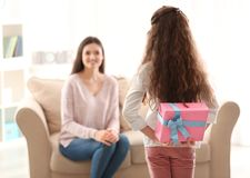 Little girl hiding gift box for mom behind her back. Indoors. Mother`s day celebration Stock Image