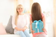 Little girl hiding gift box for Mother`s Day. Behind her back at home Royalty Free Stock Image