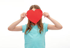 Little girl hiding her face behind red paper heart Royalty Free Stock Image