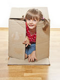 Little girl hiding inside paper box Stock Image