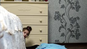 Little girl hiding and peeking out from behind the bed