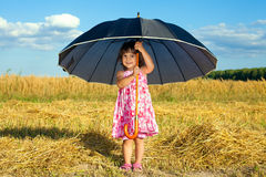 Little girl hiding under big umbrella Royalty Free Stock Photography