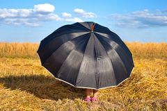 Little girl hiding under umbrella Stock Photography