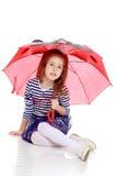 Little girl hiding under an umbrella. Stock Photo