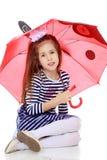 Little girl hiding under an umbrella. Stock Images