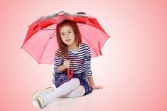 Little girl hiding under an umbrella. Stock Photos