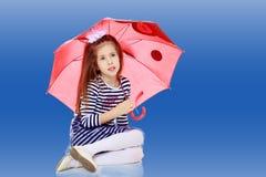 Little girl hiding under an umbrella. Royalty Free Stock Image