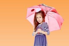 Little girl hiding under an umbrella. Royalty Free Stock Photos