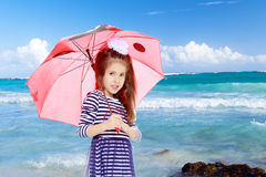 Little girl hiding under an umbrella. Stock Image