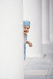 Little girl hiding in columns Stock Images