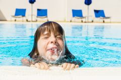 Little girl in an outdoor pool. Little girl with his eyes closed and spitting water coming out of the water in an outdoor pool royalty free stock image