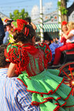 Little girl with his father, Seville Fair, Andalusia, Spain. Andalusian little girl with traditional flamenco dresses on the shoulders of his father during the stock image