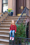 Little girl in historic district of West Village. Old houses with stairs in historic district of West Village Royalty Free Stock Images