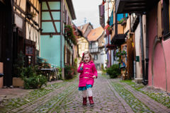 Little girl in historical city center in France. Cute little girl in pink coat walking down a street in historical medieval city center on cold autumn day. Child stock photo