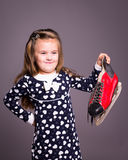 Little girl with hockey players skate in the hand. Little girl with beautiful long hair, hockey players skate in the hand Royalty Free Stock Image