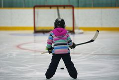 Little girl without hockey stick, staring at a hockey net. The back e of a five year old girl in hockey equipment shooting a puck on an empty hockey net Stock Images
