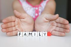 Little girl hold toy blocks. Protect your family concept. Little girl hold toy blocks with word Family. Protect your family concept. Word Family made of plastic Royalty Free Stock Image