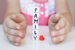 Little girl hold toy blocks. Protect your family concept. Little girl hold toy blocks with word Family. Protect your family concept. Word Family made of plastic Royalty Free Stock Photos